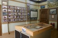 View of Waiting Vestibule (G7) looking north east showing the display of wall mounted photographs depicting the works between 1938 and 2002 and a the plan chests  of documents between 1790 and 2002.