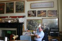 "View of room (G6) the ""Boardroom"" looking south west showing photographs, paintings and artefacts. Iin the photograph is Noel Evans a trustee of the EVWAT and a volunteer of the EVWM.."